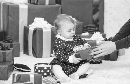 Baby first christmas once in lifetime event. Little baby play near pile of wrapped red gift boxes. Gifts for child first christmas. My first christmas. Sharing joy of baby first christmas with family