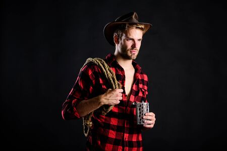 Sheriff concept. Brutal cowboy drinking alcohol. Western culture. Man wearing hat hold rope and flask. Lasso tool of American cowboy. Man handsome unshaven cowboy black background. Western life Reklamní fotografie