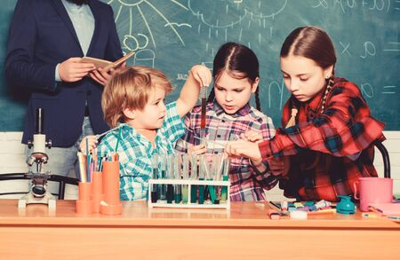 Smart and confident. happy children teacher. back to school. experimenting with chemicals or microscope at laboratory. biology education. Microscope. Biology school laboratory equipment