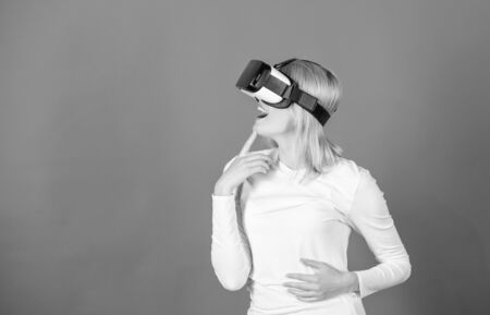 Woman with virtual reality headset. Happy young woman wearing virtual reality goggles watching movies or playing video games. Pretty woman playing game in virtual reality glasses.