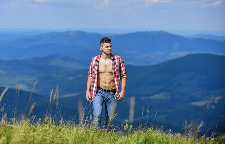 Muscular tourist walk mountain hill. Hiker muscular torso reach mountain peak. Hiking concept. Man stand top mountain landscape background. Athlete guy relax mountains. Beautiful environment