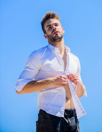 Attractive man taking off shirt. Confident in his appealing. Bearded guy business style. Handsome man fashion model. Sexy macho man. Hot day outdoors. Heat season. Formal fashion. Formal style