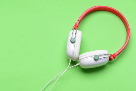 Headphones in white and red color with wire. Hobby, leisure and music concept. Modern and stylish earphones isolated on light green background, top view, copy space. Headset for music made of plastic 写真素材