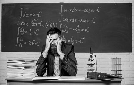 Teaching dumb students. No hope for better. Tired and exhausted. Teacher mature man. Fed up. Difficult work. Emotional burnout. Teacher give up. Hate his job. Man desperate teacher in classroom.