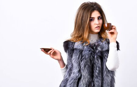 Woman splendid makeup wearing luxurious fur coat drinking hot coffee. Pretty lady drink coffee little ceramic cup white background. Elite coffee concept. Enjoy luxurious aroma and taste hot coffee