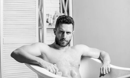 Macho naked in bathtub. Wash off foam with water carefully. Sex and relaxation concept. Macho attractive nude guy. Sexy man in bathroom. man wash muscular body with foam sponge. massage relaxation Stock Photo