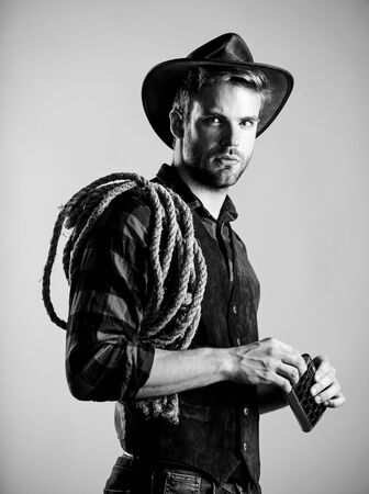 have a drink. wild west rodeo. man in hat drink whiskey. man checkered shirt on ranch. cowboy with lasso rope. Western. Vintage style man. Wild West retro cowboy. western cowboy portrait
