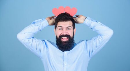Being heads over heals. Hipster with small hearts. Bearded man holding red hearts on head. Sexy valentine man with heart shaped cards. Happy valentines day. Expressing his love