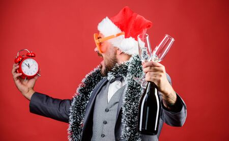 Join office party. Winter party ideas. Almost midnight. Time to celebrate new year. Christmas party. Man bearded hipster santa hat champagne bottle. alarm clock. Corporate party. Cheers concept.