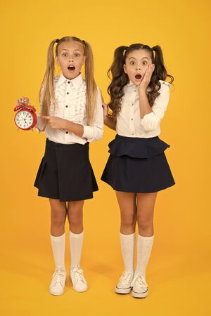 OMG. Got a surprise. Surprised schoolgirls checking time on yellow background. Shocked little children having mouth open with surprise being late. Back to school surprise. Surprise concept