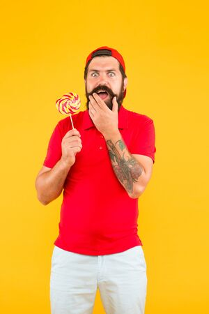 Calorie and diet. happy hipster love sweet food. diet and calorie. Man with lollipop and smile. brutal bearded man in uniform. care about healthy smile. sweet taste. Man eat big colorful lollipop Reklamní fotografie