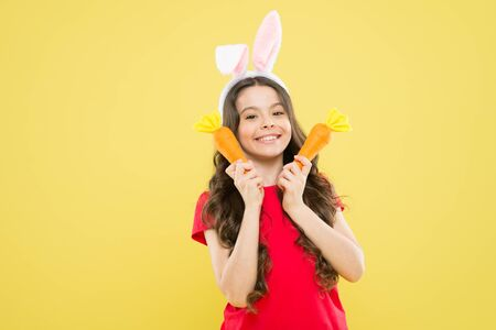 Health in her hands. small girl hold carrot. child in bunny ears. nutrition diet for health. benefit of eateing carrot. easter carrot recipes. stay healthy and happy. Healthy eating for her 版權商用圖片