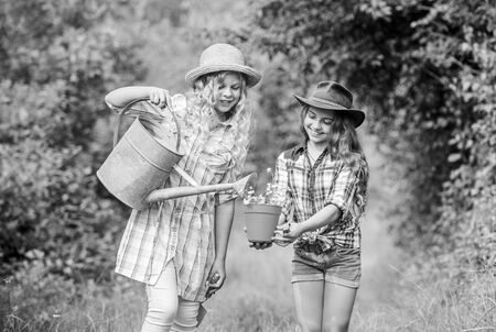 earth day. summer family farm. small girls farmer in village. ecology and environmental protection. children hold gardening tools. farming and agriculture. spring country side. watering flower