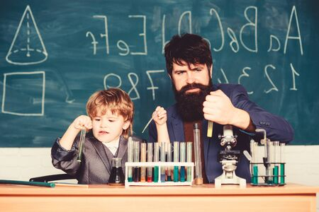 Laboratory test tubes and flasks with colored liquids bearded man teacher with little boy. laboratory research and development. father and son child at school. Chemistry experiment. Pushing Limits