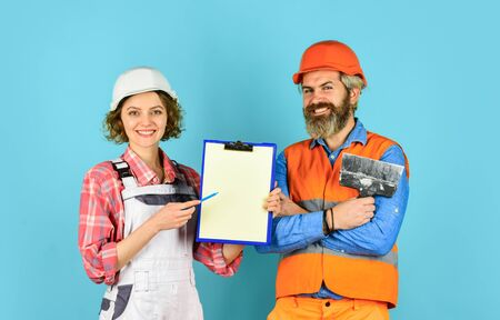 Price list. Couple look documents. Couple planning changes renovation apartment. Renovation concept. Woman and man safety hard hat. Discussing renovation with contractor. Sign contract with workers Archivio Fotografico