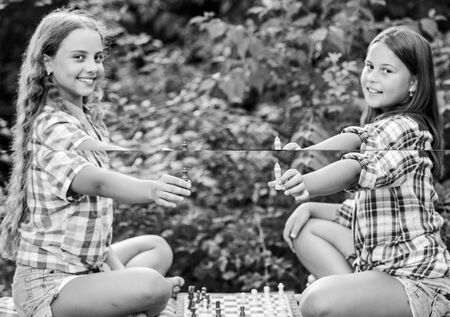 dont be a pawn. wunderkind. make the brain work. early childhood development. worthy opponents. develop hidden abilities. two concentrated girls play chess. chess playing sisters. child prodigies