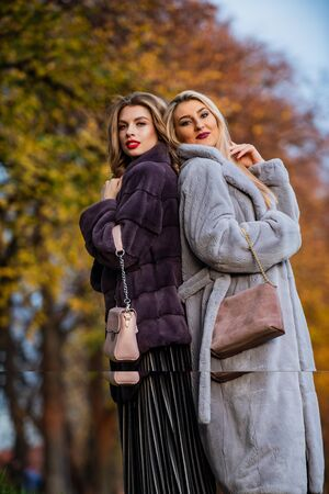 Feeling flirty.women wear fur coat. trendy winter look. No Compromise on Comfort. Man-made fur is prone to shedding. fake fur from reputable brand. elegant girls in autumn park. beauty and fashion