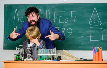 Back to class is cool. using microscope in lab. Back to school. teacher man with little boy. school lab equipment. student doing science experiments with microscope in lab. father and son at school Stock fotó