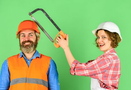 Renovation is struggle. Annoying edits. Couple renovating home. Man and woman wear safety helmet. Home Renovation. She is sawing him. Hand Saw tool. Sawing husband head. Annoyed by her actions