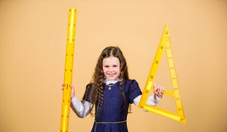 Sizing and measuring. Pupil cute girl with big ruler. School student study geometry. Kid school uniform hold ruler. I love mathematics. Education and school concept. Smart and clever concept