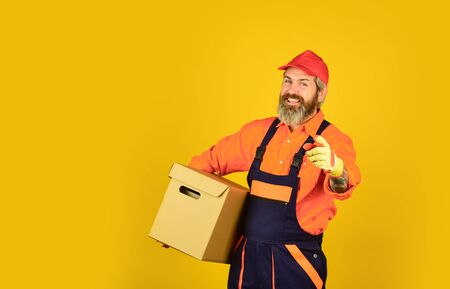 happy man cardboard box. carrying boxes inside the building. unpacking moving boxes. new house at moving day. Man builder in boilersuit hold boxes. moving to new apartment. copy space Фото со стока