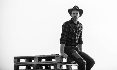 from the country. Vintage style man. Wild West retro cowboy. cowboy sit on woden pallet. Western. man checkered shirt on ranch. western cowboy portrait. wild west rodeo. Thoughtful man in hat relax