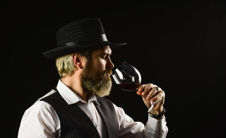 alcohol beverage. Elegant waiter drink red wine. working in wine cellar. bar or winery. wine degustation. Bearded businessman in elegant suit with glass of wine. Sommelier tastes expensive drink.