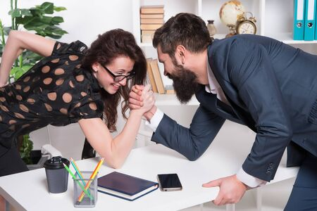 Whos stronger. Bearded man and woman arm wrestle in office. Workplace relationship. Competitive relationship. Relationship between business partners. Professional couple. Relationship or rivalry
