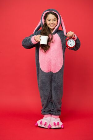 time to wake up. Drinking coffee energy. good morning to you. little girl wear easter bunny costume. Early rise with cup of coffee. happy kid in kigurumi pajama hold alarm clock