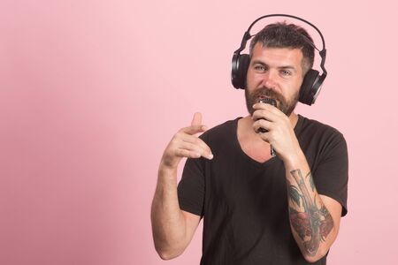 Dj with beard wears headphones. Singer with beard
