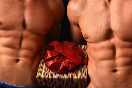 Athletes in close up holding striped gift box with red bow for Christmas. Male twins with naked torso on black background. Sports, holidays and surprise concept. Guys abs and strong chests.
