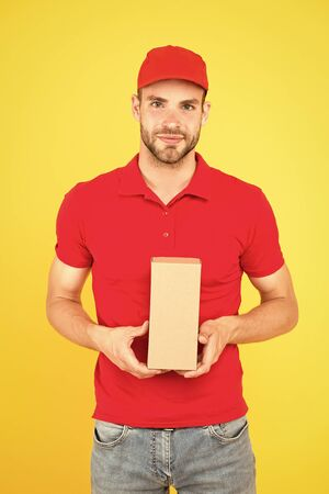 Faster than you can imagine. Delivered to your destination. Service delivery. Salesman career. Courier and delivery. Postman delivery worker. Man red cap yellow background. Delivering purchase Foto de archivo - 143640286