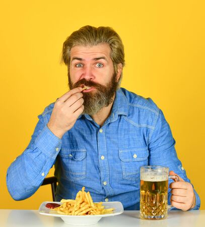 lazy man enjoying fresh beer and junk food. man with fast food. beer and french fries in restaurant. eating and drinking at bar. hipster relax in tavern. bearded guy having snack