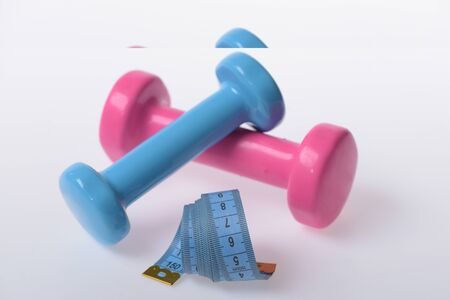 Dumbbells made of blue and pink plastic on white background. Healthy lifestyle and sports concept. Barbells next to cyan measure tape, close up. Health regime and fitness symbols, defocused