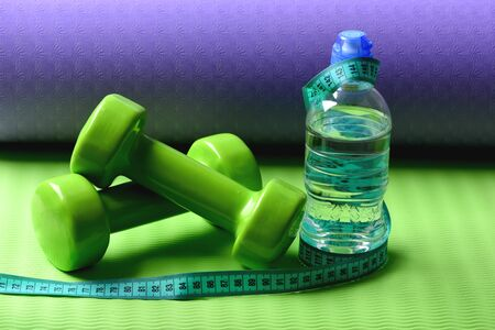 Shaping and fitness equipment. Barbells near cyan measuring tape roll and water bottle. Sports and healthy lifestyle concept. Dumbbells made of green plastic on green and purple texture background