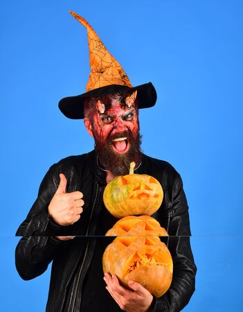 Monster with October decorations. Demon with horns and happy face holds jack o lanterns and shows thumbs up. Halloween spooky party concept. Man in witchers hat holds pumpkins on blue background