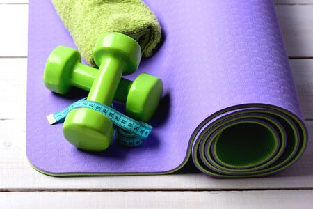 Shaping and fitness equipment. Dumbbells made of green plastic on light wooden background. Workout and sport concept. Barbells near cyan measuring tape roll and towel lying on purple yoga mat Stock Photo