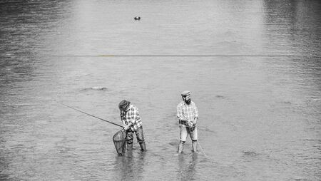 Summer weekend. Happy fisherman with fishing rod and net. Hobby and sport activity. Fishing together. Teach man to fish and you feed him for lifetime. Male friendship. Father and son fishing Banco de Imagens