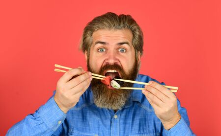 Sushi rolls. Japanese cuisine. Asian meal. Sushi roll. Man eat sushi chopsticks. Eastern culture. Bearded hipster eating rolls. Japanese food delivery. Pickled ginger served with sushi or sashimi