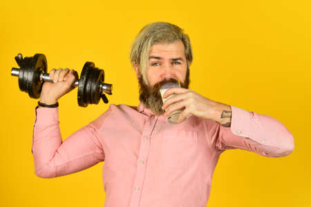 Exercise in gym. Milk good nutrients. Amount of fat. Vitamins for muscles. Sportsman hold dumbbell and glass of milk. Protein diet. Protein cocktail. Source of calcium. Bearded man drink milk