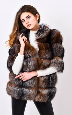 Fur store model posing in soft fluffy warm coat. Pretty fashionista. Fur fashion concept. Woman makeup and hairstyle posing mink or sable fur coat. Winter elite luxury clothes. Female brown fur coat Banco de Imagens