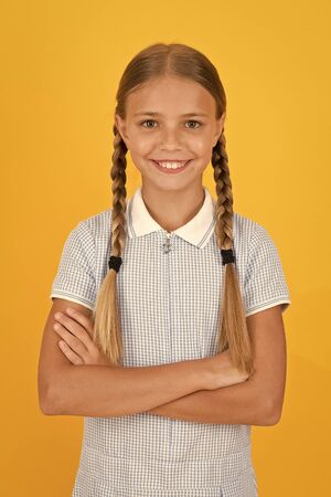 Emotional intelligence describes ability monitor your own emotions. Smiling girl. Adorable schoolgirl yellow background. Little girl. Happy childrens day. Tidy girl nice hairstyle. Positive emotions 版權商用圖片