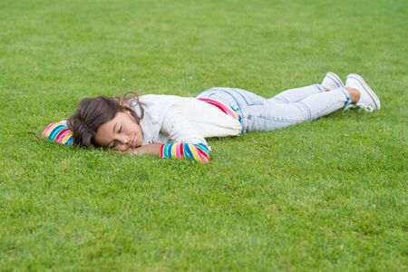 Healthy sleep on fresh air. happy child lying on grass. dream. small girl relax on green grass. spring is here. human and nature concept. kid enjoy summer season. childhood happiness. have a good day