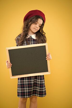 education concept. happy girl in french beret. advertising board for promotion. school shopping sales. child on yellow background. back to school. small girl kid with school backboard, copy space