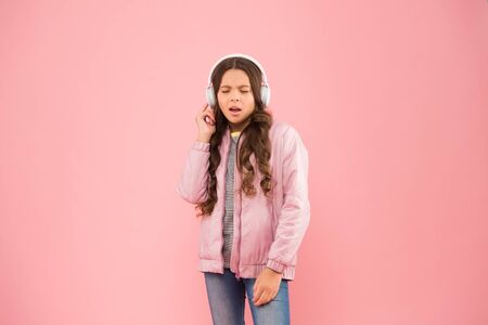 Full enjoyment. Singing along to tune. Happy child enjoy listening to sound track. Little girl wear earphones pink background. Enjoy sound. Sound vibrations. Music and technology. Audio sound Фото со стока