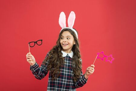 Eyewear booth props. Little cute bunny. Having fun. Schoolgirl bunny ears. Girl in Easter bunny at egg hunt. Party and social event. Family holiday. Traditional party activities. Smart bunny