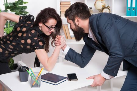 Gender equality. Career in business. Worthy rival. Underestimate forces. Equal rights. Feminism concept. Business competition. Business leadership. Man and woman tense faces compete armwrestling Standard-Bild
