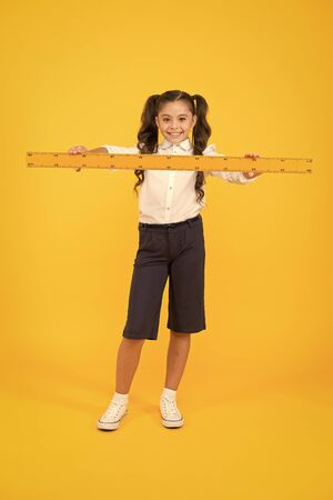 Studying is fun. School adorable student study geometry. Kid school uniform hold ruler. Pupil cute girl with big ruler. Geometry school subject. Education and school concept. Sizing and measuring