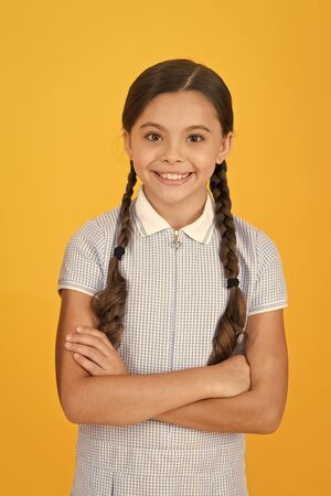 old school fashion. back to school. happy beauty on yellow background. happy childhood. hair health concept. girl with long hair. smart girl in vintage dress. little girl retro uniform. Knowledge day