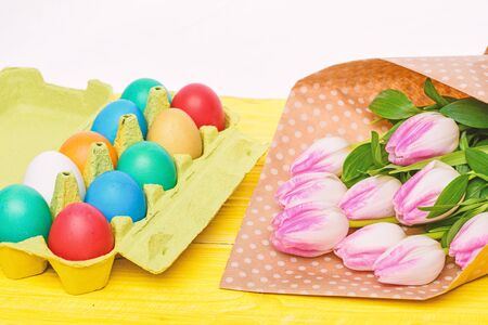 painted eggs in egg tray. Happy easter. Spring holiday. Holiday celebration, preparation. Egg hunt. Tulip flower bouquet. Healthy and happy holiday. Look over there. Reklamní fotografie